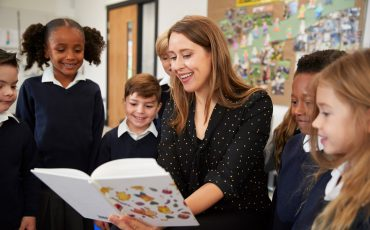 female-primary-school-teacher-reading-to-a-class-C65QJRL.jpg