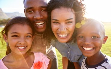 laughing-black-family-outdoors-close-up-back-lit-PPCMZD4.jpg